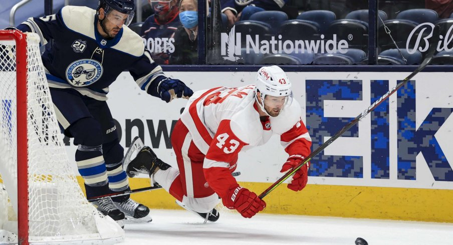 May 7, 2021; Columbus, Ohio, USA; Columbus Blue Jackets defenseman Michael Del Zotto (15) skates against Detroit Red Wings left wing Darren Helm (43) for the loose puck in the second period at Nationwide Arena.
