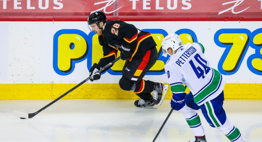 Elias Lindholm protects the puck from Elias Pettersson