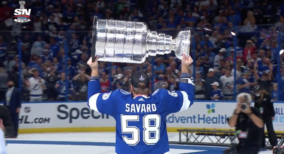 David Savard lifts the Stanley Cup above his shoulders.