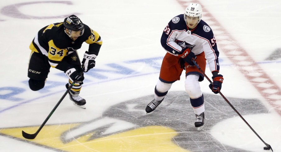 Sep 27, 2021; Pittsburgh, Pennsylvania, USA; Columbus Blue Jackets forward Yegor Chinakhov (59) moves the puck against Pittsburgh Penguins forward Nathan Legare (34) during the third period at PPG Paints Arena. The Blue Jackets won 3-0.