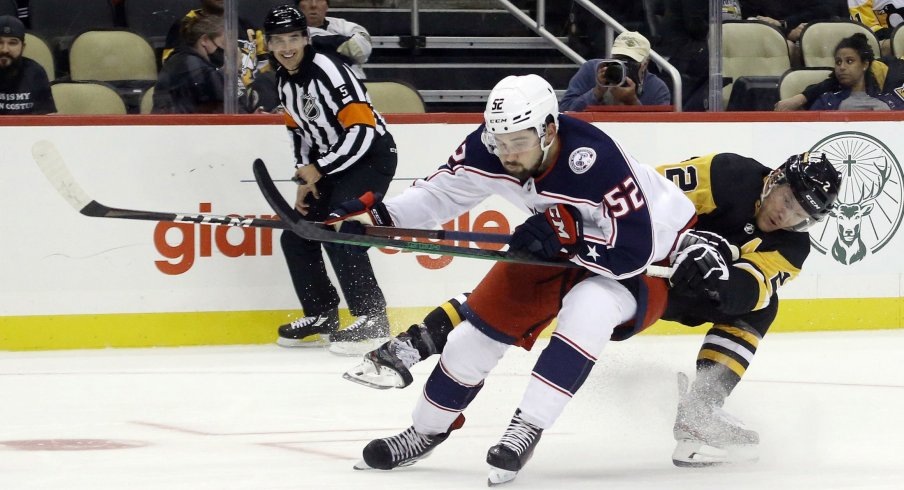 Sep 27, 2021; Pittsburgh, Pennsylvania, USA; Columbus Blue Jackets center Emil Bemstrom (52) skates with the puck around Pittsburgh Penguins defenseman Chad Ruhwedel (2) during the second period at PPG Paints Arena.